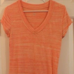 Orange and white striped, short sleeved shirt.